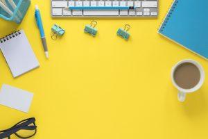overhead view keyboard eyeglasses tea cup yellow workspace